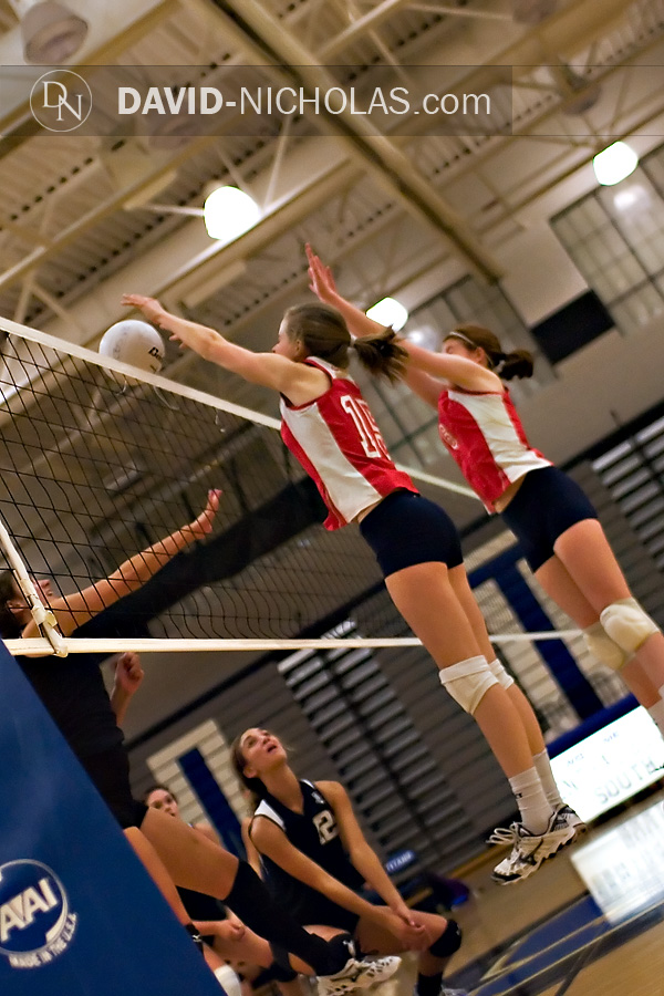 Lady Patriot Christine Gilbert (15) penetrates Lady Titan space above the net to block the attack, while teammate Grace Patterson (6) provides additional blocking support.