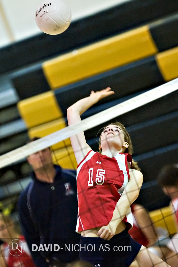 Lady Patriot Christine Gilbert (15) sends a power kill shot across to her C.B. West opponents as Coach Headly (in the background) observes the action.